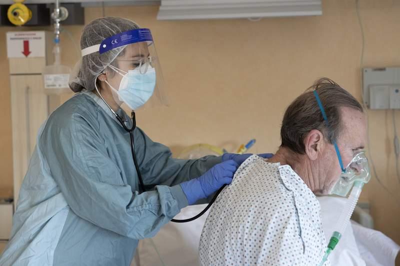 Dr. Elisabetta Teti visits COVID-19 patient 67-year-old Roberto Tortosa, in a sub-intensive COVID-19 unit of the Tor Vergata Polyclinic Hospital, in Rome, Saturday, Nov. 7, 2020. (AP Photo/Alessandra Tarantino)