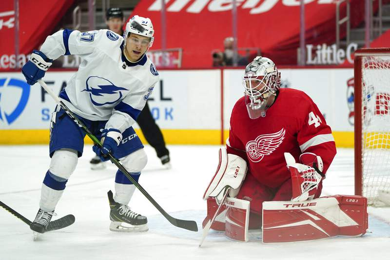 Tampa Bay Lightning center Yanni Gourde (37) watches the puck in front of Detroit Red Wings goaltender Jonathan Bernier (45) in the third period of an NHL hockey game Thursday, March 11, 2021, in Detroit. (AP Photo/Paul Sancya)