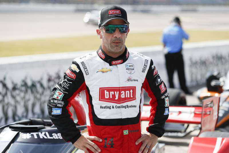 FILE - In this July 17, 2020, file photo, driver Tony Kanaan, of Brazil, stands next to his car during qualifying for an IndyCar Series auto race at Iowa Speedway in Newton, Iowa. Kanaans supposed farewell tour last year fizzled amid nearly empty tracks. Then he was given another chance to extend his IndyCar career, this time before fans. His first two races come this weekend at Texas Motor Speedway. (AP Photo/Charlie Neibergall, File)