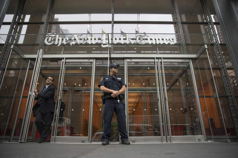 FILE - In this June 28, 2018, file photo, a police officer stands outside The New York Times building in New York. The Trump Justice Department secretly obtained the phone records of four New York Times journalists as part of a leak investigation, the newspaper said Wednesday, June 2, 2021. (AP Photo/Mary Altaffer, File)