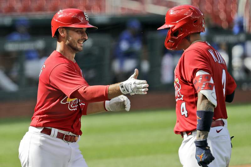 FILE - In this Wednesday, July 22, 2020, file photo, St. Louis Cardinals' Paul DeJong, left, is congratulated by teammate Yadier Molina after hitting a two-run home run during the fifth inning of an exhibition baseball game against the Kansas City Royals in St. Louis. The Cardinals announced Tuesday, Aug. 4, 2020, that DeJong and Molina are among six of the players who have tested positive for coronavirus. The others are infielders Edmundo Sosa and Rangel Ravelo, and pitchers Junior Fernandez and Kodi Whitley.(AP Photo/Jeff Roberson, File)