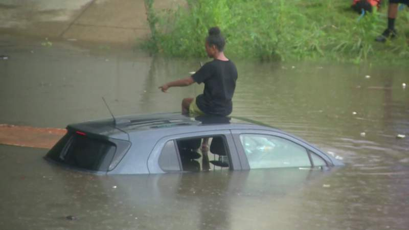 Angel Johnson sits on the roof of her SUV after it got stuck on a flooded Southfield Freeway on Aug. 27, 2021.