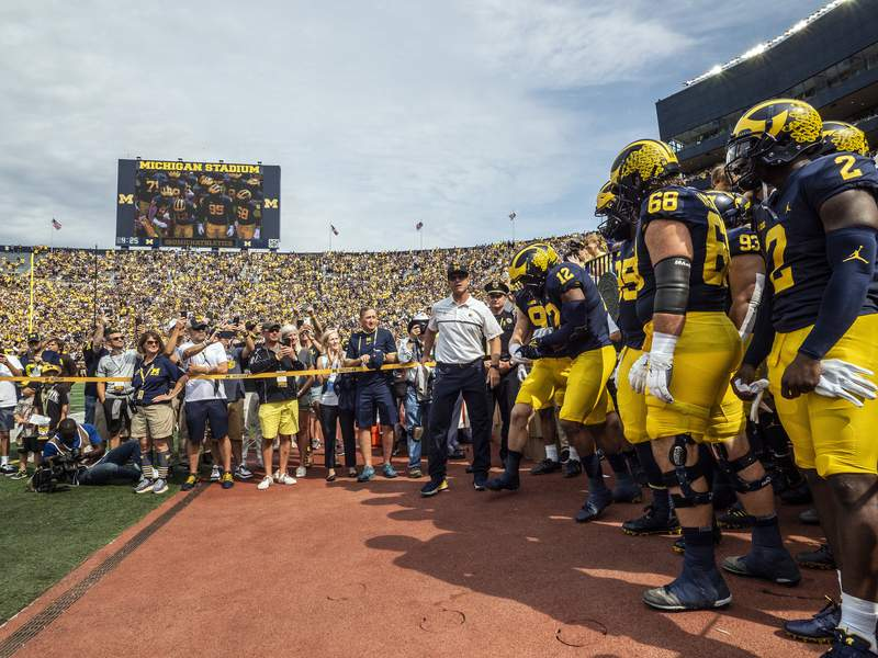 Michigan head coach Jim Harbaugh, center, prepares to take to the Michigan Stadium field with his team before an NCAA college football game against Western Michigan in Ann Arbor, Mich., Saturday, Sept. 4, 2021. (AP Photo/Tony Ding)