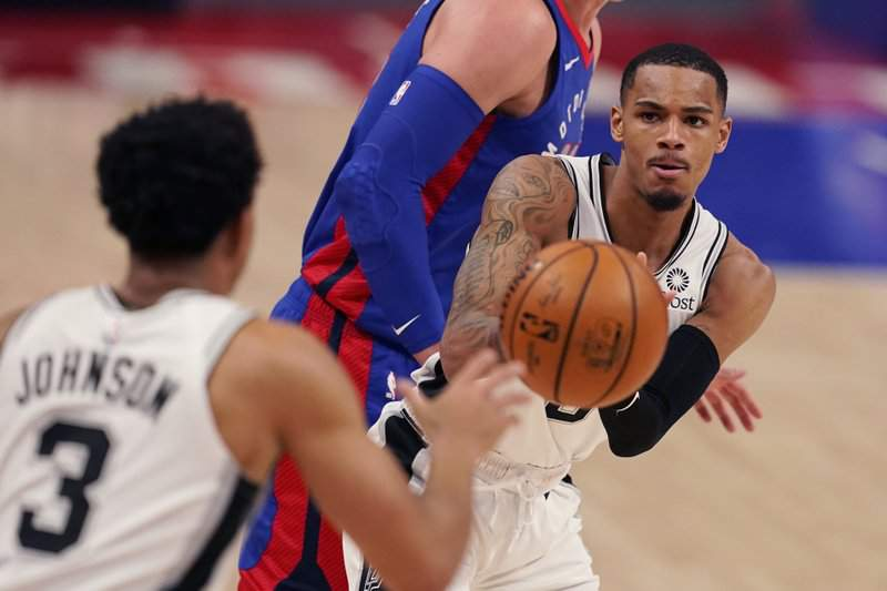 San Antonio Spurs guard Dejounte Murray passes to forward Keldon Johnson (3) during the second half of an NBA basketball game against the Detroit Pistons, Monday, March 15, 2021, in Detroit.