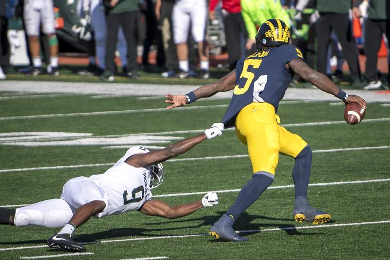 Dominique Long #9 of the Michigan State Spartans misses a tackle on Joe Milton #5 of the Michigan Wolverines during the fourth quarter at Michigan Stadium on October 31, 2020 in Ann Arbor, Michigan.