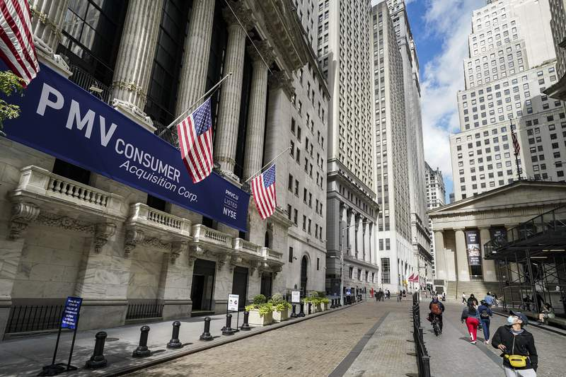 FILE - Pedestrians pass the New York Stock Exchange, Friday, Oct. 2, 2020, in New York.   Stocks are opening broadly higher on Wall Street, following global markets higher on Election Day in the U.S. The S&P 500 rose 1% in the early going Tuesday, Nov. 3. (AP Photo/John Minchillo)
