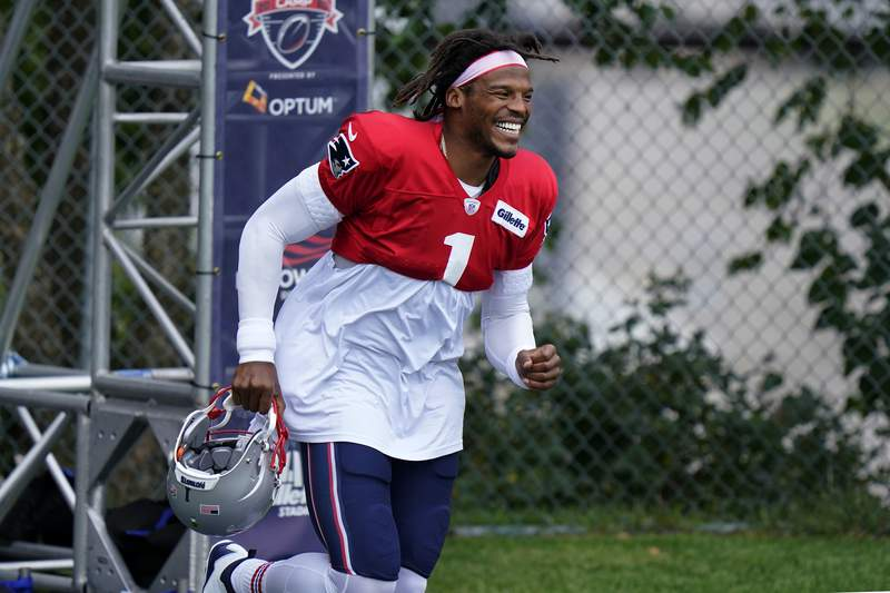 New England Patriots quarterback Cam Newton smiles as he steps on the field at the start of an NFL football training camp practice, Thursday, Aug. 27, 2020, in Foxborough, Mass. (AP Photo/Steven Senne, Pool)