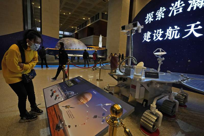 """A visitor to an exhibition looks at a display with a replica of the Chinese Mars Rover of the Tianwen-1 spacecraft in Beijing on March 12, 2021. China's National Space Agency confirmed Wednesday, March 31, 2021 that it had working-level meetings and communications with NASA from January to March to ensure the flight safety"""" of their crafts. (AP Photo/Ng Han Guan)"""