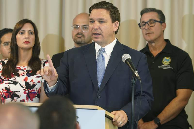 In this Aug. 10, 2021, photo, Florida Gov. Ron DeSantis answers questions related to school openings and the wearing of masks in Surfside, Fla. Top Republicans are battling school districts in their own states urban, heavily Democratic areas over whether students should be required to mask up as they head back to school. (AP Photo/Marta Lavandier)