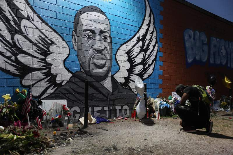 Joshua Broussard kneels in front of a memorial and mural that honors George Floyd at the Scott Food Mart corner store in Houston's Third Ward, where Floyd grew up, on June 8, 2020 in Houston. Floyd died May 25 while in Minneapolis police custody, sparking nationwide protests.