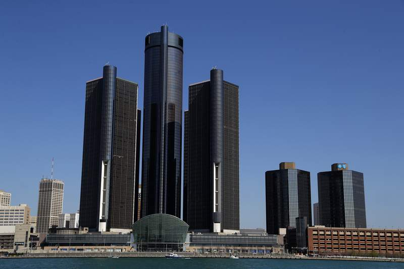 This May 12, 2020, photo shows a general view of the Renaissance Center, headquarters for General Motors, along the Detroit skyline from the Detroit River. A federal judge in Detroit dismissed General Motors lawsuit Wednesday, July 8, 2020, alleging that rival Fiat Chrysler paid off union leaders to get better contract terms than GM. (AP Photo/Paul Sancya)