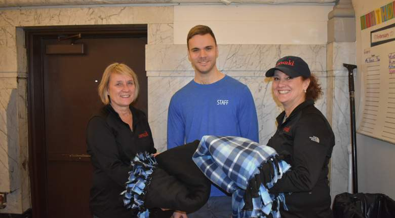 Oswald Companies' Ann Roshak and Lisa Pape present Pope Francis Center staffer John Fitzgerald with a few of the fleece blankets they and their co-workers made.