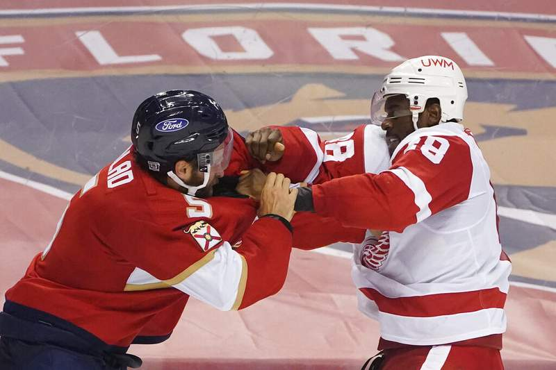 Florida Panthers defenseman Aaron Ekblad, left, and Detroit Red Wings right wing Givani Smith fight during the third period of an NHL hockey game, Sunday, Feb. 7, 2021, in Sunrise, Fla. (AP Photo/Wilfredo Lee)
