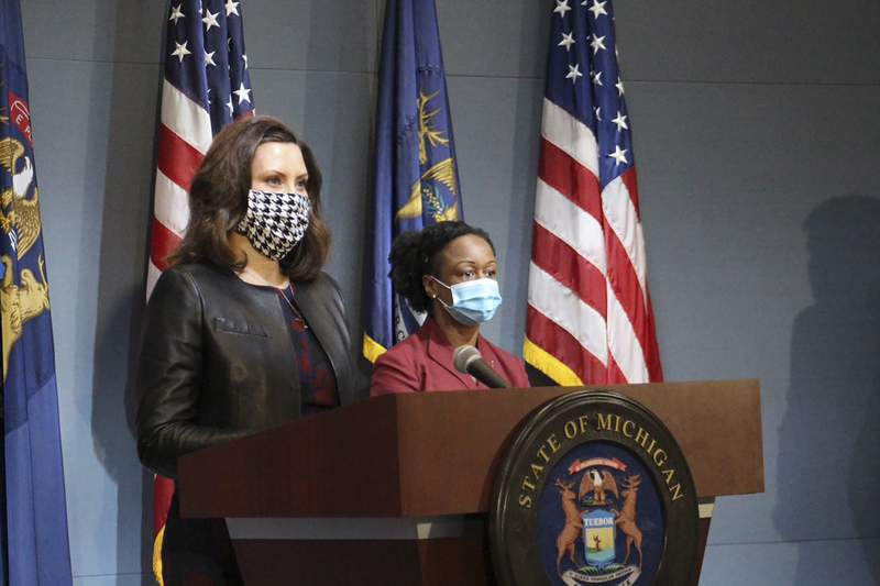 In a pool photo provided by the Michigan Office of the Governor, Michigan Gov. Gretchen Whitmer, wearing a mask, addresses the state during a speech in Lansing, Mich., Friday, May 1, 2020. The governor said Michigan's stay-at-home order remains in effect despite Republicans' refusal to extend her underlying coronavirus emergency declaration, as she amended it to allow construction, real estate and outdoor work to resume next week. (Michigan Office of the Governor via AP, Pool)