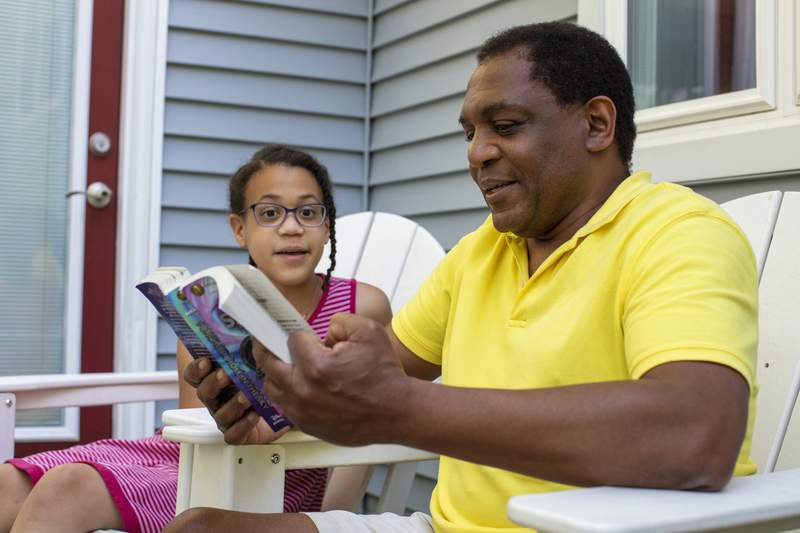 Andrew Grant-Thomas reads to his daughter, Lena Grant-Giraud, on the back porch at their home in Amherst, Mass., on Monday, May 24, 2021. Grant-Thomas and his wife, Melissa Giraud, started the nonprofit EmbraceRace in 2016 when they found few resources to help them talk with their young daughters about race. The nonprofits approach, Grant-Thomas says, can be summed up in a simple mantra: Start young, and keep going. (M. Scott Brauer/Chronicle of Philanthropy via AP)