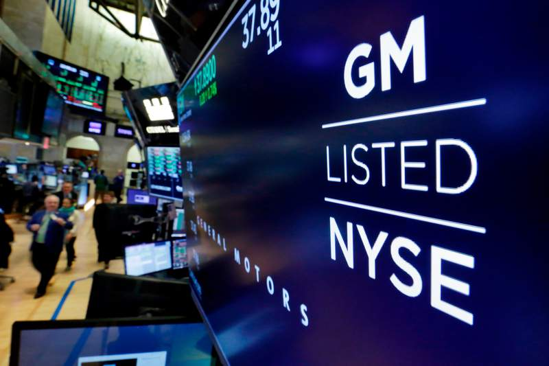 FILE - In this April 23, 2018, file photo, the logo for General Motors appears above a trading post on the floor of the New York Stock Exchange.  General Motors net profit fell 4.5% in 2020, but a strong second half more than offset the effects of pandemic-related factory closures and a costly air bag recall. The Detroit automaker said Wednesday, Feb. 10, 2021  it made $6.43 billion as demand for its vehicles surged late in a year dominated by coronavirus upheaval.  (AP Photo/Richard Drew, File)