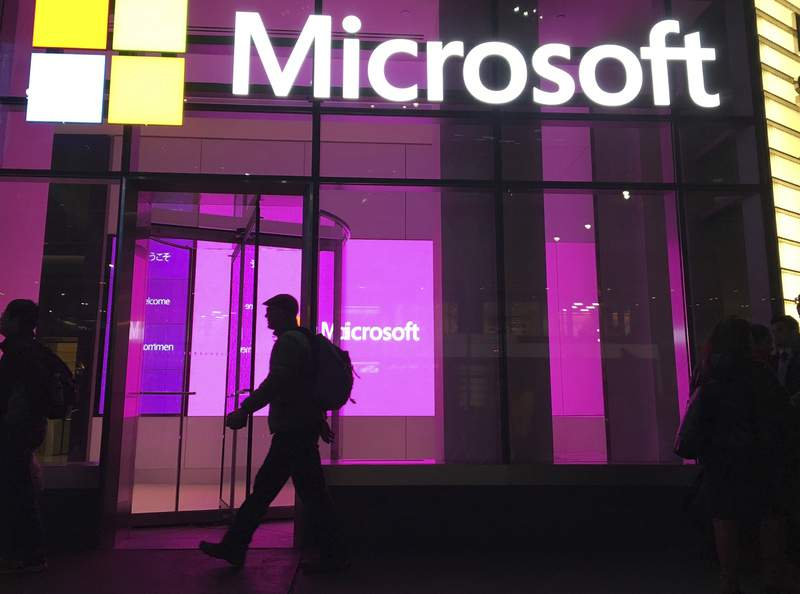 FILE - In this Nov. 10, 2016, file photo, people walk past a Microsoft office in New York. China-based government hackers have exploited a bug in Microsoft's email server software to target U.S. organizations, the company said Tuesday, March 2, 2021. (AP Photo/Swayne B. Hall, File)