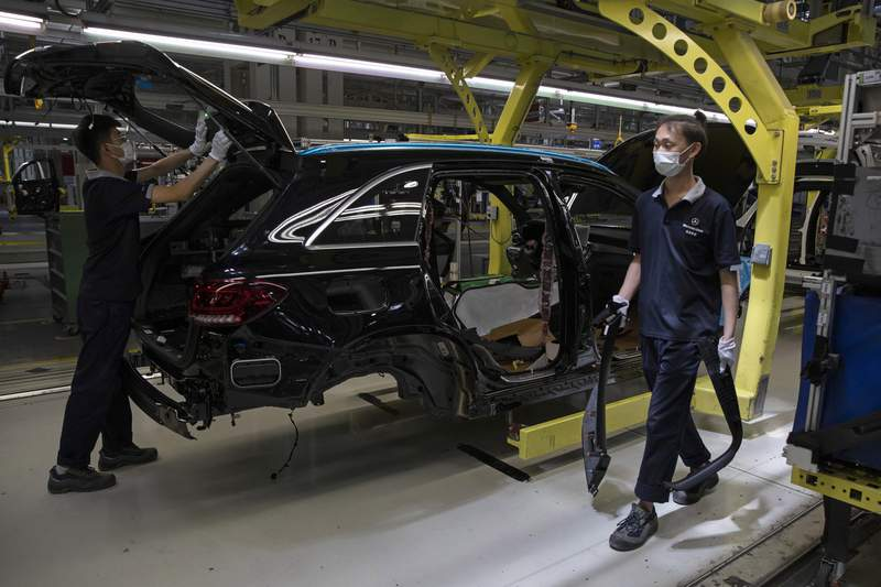 In this Wednesday, May 13, 2020, photo, workers assemble cars at a factory for the joint venture company Beijing Benz Automotive Co., Ltd in Beijing. Factory output rose in April as China's virus-battered economy reopened but job losses depressed consumer spending, a key driver of growth, in a sign of the challenges the ruling Communist Party faces in reviving normal activity. (AP Photo/Ng Han Guan)