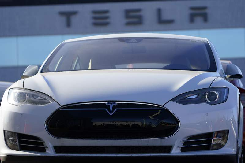 An unsold 2021 S70 sedan sits at a Tesla dealership Sunday, Nov. 8, 2020, in Littleton, Colo. Tesla will be added to the S&P 500 index on Dec. 21. Based on its market value Monday, Nov. 16, 2020, the electric car maker would be one of the top 10 companies in the benchmark index upon entry. (AP Photo/David Zalubowski)