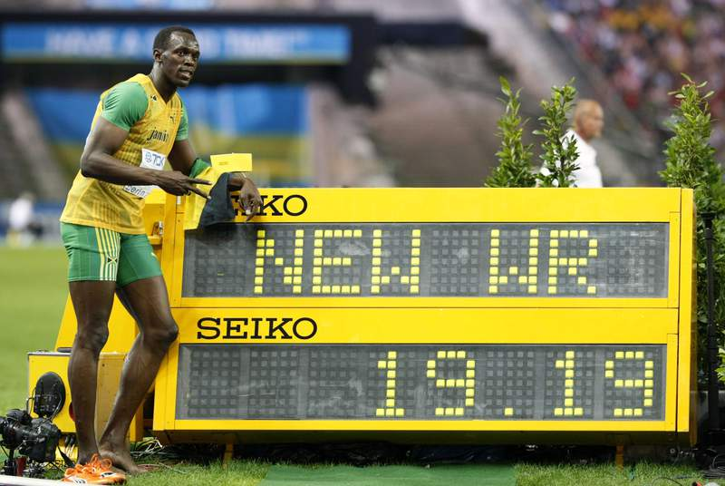FILE - In this Aug. 20, 2009, file photo, Jamaica's Usain Bolt poses beside the timing board showing the new World Record after he won the Men's 200-meter final during the World Athletics Championships in Berlin. (AP Photo/Anja Niedringhaus, File)