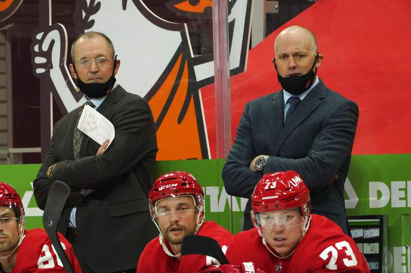 Detroit Red Wings head coach Jeff Blashill, right, and assistant coach Dan Bylsma watch against the Carolina Hurricanes in the first period of an NHL hockey game Saturday, Jan. 16, 2021, in Detroit. (AP Photo/Paul Sancya)