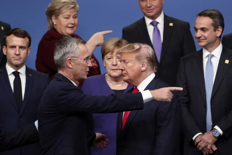 FILE - In this Dec. 4, 2019, file photo, NATO Secretary General Jens Stoltenberg, front left, speaks with U.S. President Donald Trump, front right, after a group photo at a NATO leaders meeting at The Grove hotel and resort in Watford, Hertfordshire, England. There will be leaders and populations who shudder at the thought of four more years of the Donald Trump administration and those whose consternation is tied to his potential defeat, and a U.S. government led by a President Joe Biden. (AP Photo/Francisco Seco, File)
