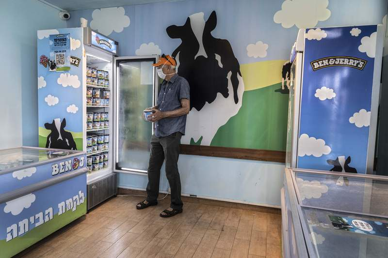 FILE - In this Tuesday, July 20, 2021 file photo, an Israeli shops at the Ben & Jerry's ice-cream factory in the Be'er Tuvia Industrial area, southern Israel. Alan Jope the CEO of Unilever on Thursday, July 22, 2021, said the global consumer goods giant remains fully committed to doing business in Israel, distancing himself from this week's announcement by the company's Ben & Jerry's ice cream brand to stop serving Israel's West Bank settlements. Jope gave no indication that Unilever would force Ben & Jerry's to roll back its controversial decision. (AP Photo/Tsafrir Abayov, File)