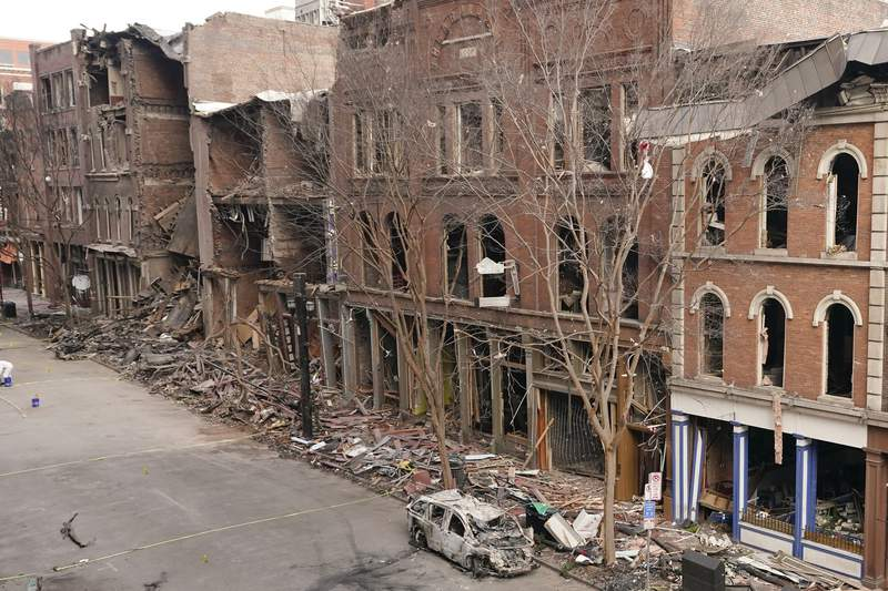 A vehicle destroyed in a Christmas Day explosion remains on the street Tuesday, Dec. 29, 2020, in Nashville, Tenn. Officials have named 63-year-old Anthony Quinn Warner as the man behind the bombing in which he was killed, but the motive has remained elusive. (AP Photo/Mark Humphrey)