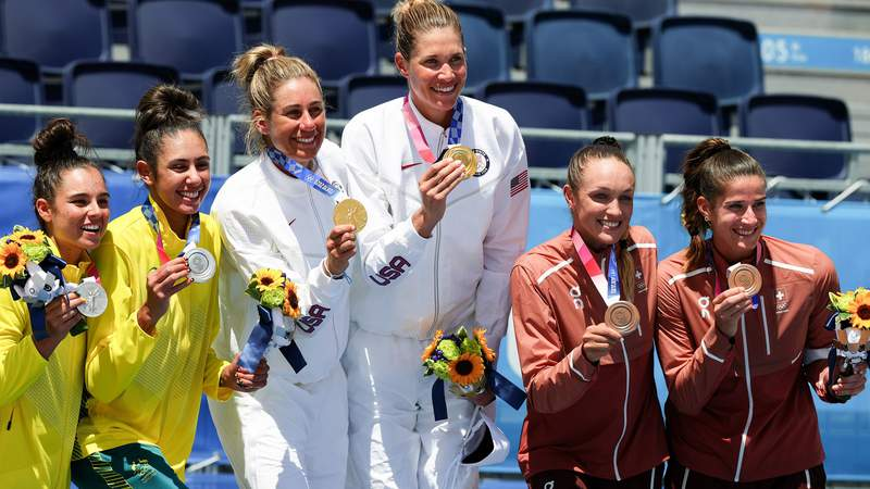 Taliqua Clancy and Mariafe Artacho Del Solar of Australia, April Ross and Alix Klineman of USA, Anouk Verge-Depre and Joana Heidrich of Switzerland cheering on the podium at the medal ceremony.