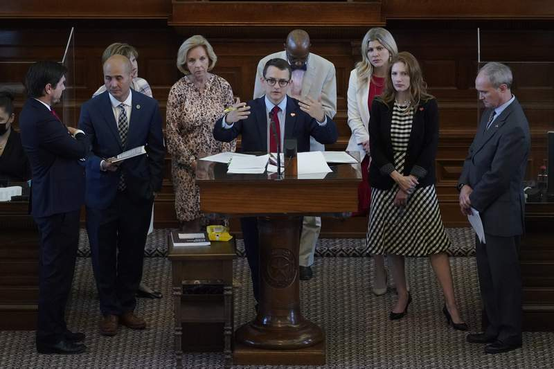Rep. Briscoe Cain, R-Houston, center, stands with co-sponsors as he answers questions and speaks in favor of HB 6, an election bill, in the House Chamber at the Texas Capitol in Austin, Texas, Thursday, May 6, 2021. (AP Photo/Eric Gay)