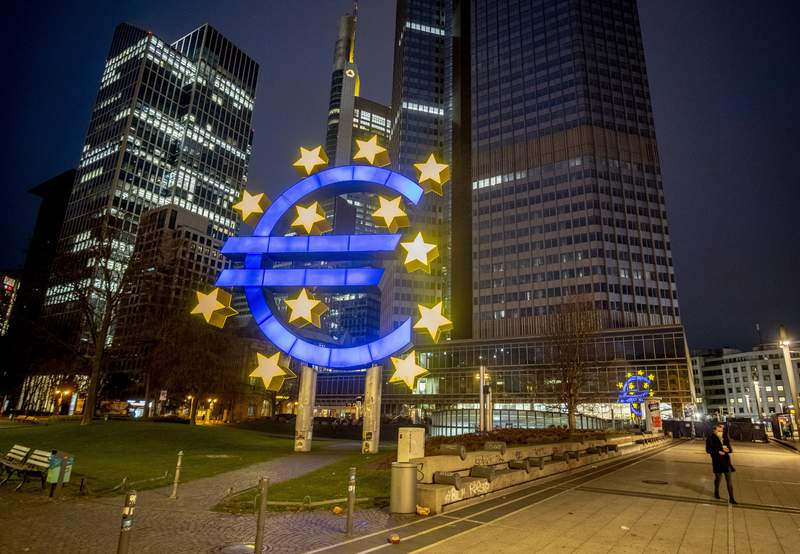 FILE - In this Thursday, March 11, 2021 file photo, a man walks past the Euro sculpture in Frankfurt, Germany.  Facing unease over the spread of a more-contagious variant of the coronavirus, the European Central Bank (ECB) said Thursday July 22, 2021, it would maintain its stimulus in the form of ultra-low interest rates until inflation durably reaches its 2% target. (AP Photo/Michael Probst, File)