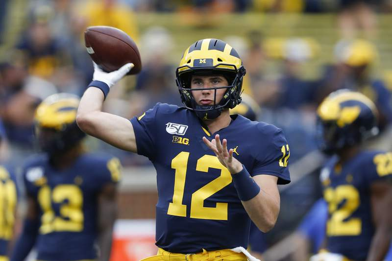 Michigan quarterback Cade McNamara throws during warmups before an NCAA college football game against Middle Tennessee in Ann Arbor, Mich.