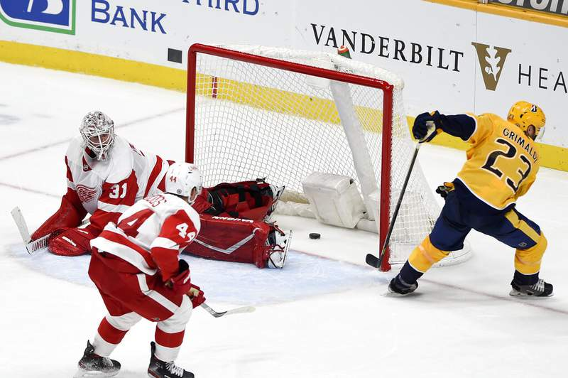 Nashville Predators right wing Rocco Grimaldi (23) scores his fourth goal of the night, this one against Detroit Red Wings goaltender Calvin Pickard (31) during the third period of an NHL hockey game Thursday, March 25, 2021, in Nashville, Tenn. The Predators won 7-1. (AP Photo/Mark Zaleski)