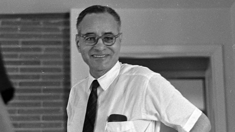 Portrait of Nobel Prize-winning political scientist and diplomat Ralph Bunche (1904 - 1971) stands smiling, with hands on hips, in the living room of the home where Dr. King spent the night in Montgomery, Alabama prior to the final day of the Selma to Montgomery march, 1965. From the Chicago Defender Collection.