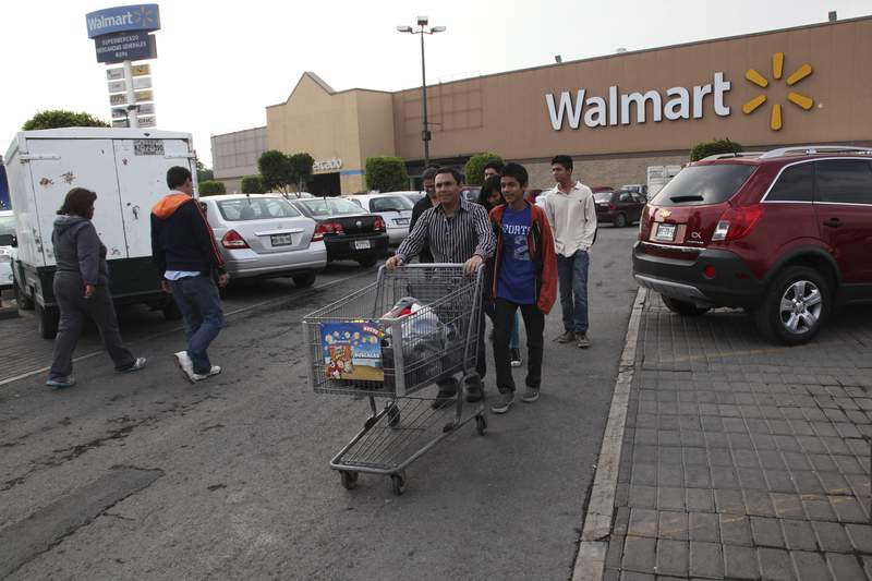 FILE - In this Dec. 26, 2013 file photo, a family leaves a local Walmart in Mexico City. Walmart de Mexico, the countrys biggest retailer, announced the week of June 18, 2021, that its grocery store baggers wouldnt be allowed back, as the coronavirus pandemic and changing consumer habits threaten to put an end to a decades-old practice of allowing elderly people in Mexico to earn extra income as baggers. (AP Photo/Marco Ugarte, File)