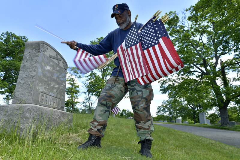 Bob Workman of Boston, a retired Marine Gunnery Sgt., and past commander of the Boston Police VFW, replaces flags at veteran's graves ahead of Memorial Day on Thursday, May 27, 2021, in the Fairview Cemetery in Boston. (AP Photo/Josh Reynolds)