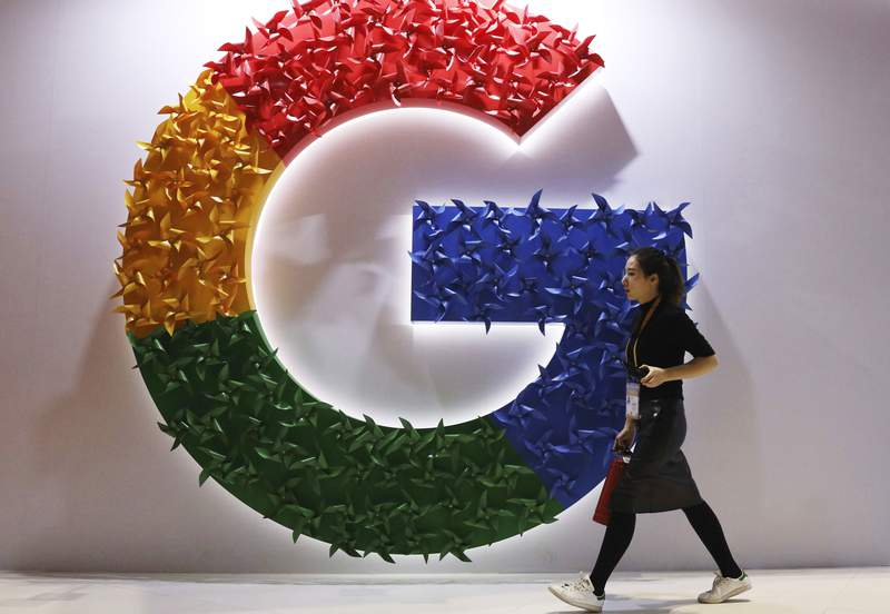 FILE - In this Monday, Nov. 5, 2018 file photo, a woman walks past the logo for Google at the China International Import Expo in Shanghai. France's anti-competition watchdog has decided to fine Google 220 million euros ($268 million) for abusing its dominant position in the complex business of online advertising. It said Monday, June 7, 2021 that the move is unprecedented. (AP Photo/Ng Han Guan, File)