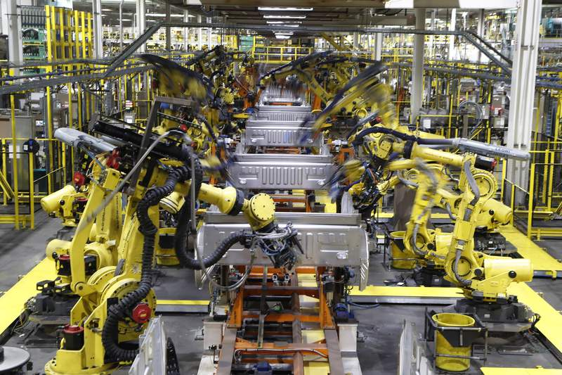 FILE - In this Sept. 27, 2018, file photo robots weld the bed of a 2018 Ford F-150 truck on the assembly line at the Ford Rouge assembly plant in Dearborn, Mich.  U.S. businesses are edging their way toward figuring out how to bring their employees back to work amid the coronavirus pandemic, some more gracefully than others. Detroit-area automakers, which suspended production in March 2020, are now pushing to restart factories as soon as possible. (AP Photo/Carlos Osorio, File)