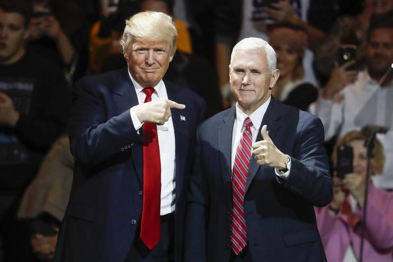 FILE - President-elect Donald Trump, left, and Vice President-elect Mike Pence acknowledge the crowd during the first stop of his post-election tour, in Cincinnati on Dec. 1, 2016. (AP Photo/John Minchillo, File)