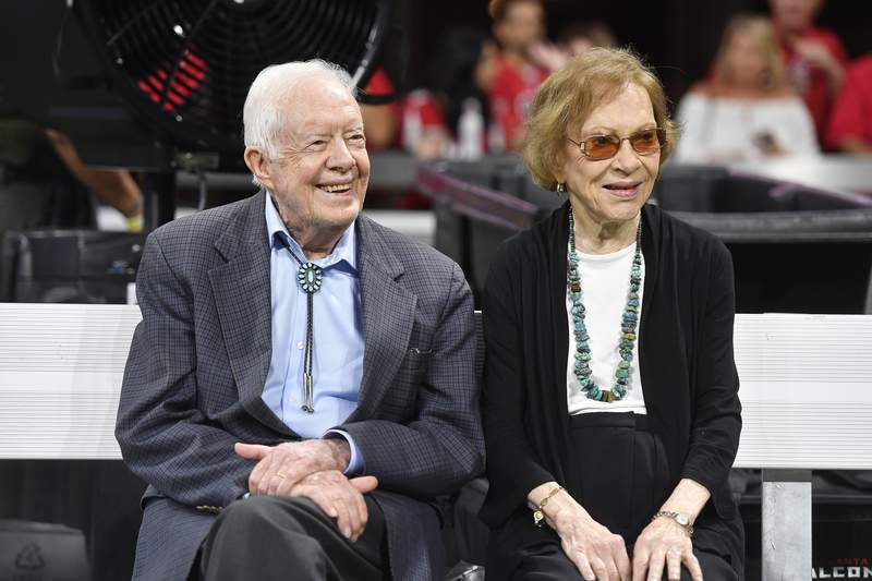 FILE- In this Sept. 30, 2018 file photo, former President Jimmy Carter and Rosalynn Carter are seen ahead of an NFL football game between the Atlanta Falcons and the Cincinnati Bengals, in Atlanta.  Former President Jimmy Carter and former first lady Rosalynn Carter will not attend President-elect Joe Bidens inauguration. It marks the first time the couple, 96 and 93, will have missed the ceremonies since Carter was sworn-in as the 39th president in 1977.(AP Photo/John Amis, File)