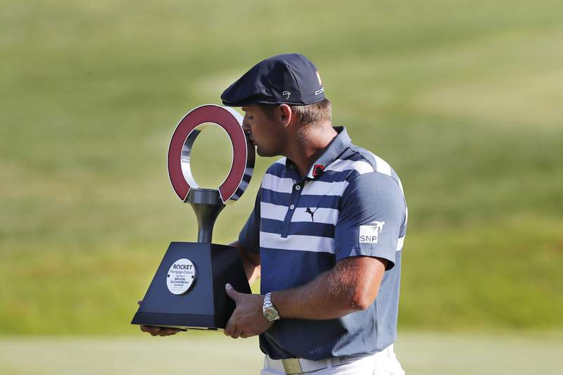 Bryson DeChambeau kisses the Rocket Mortgage Classic golf tournament trophy Sunday, July 5, 2020, at Detroit Golf Club in Detroit. DeChambeau won the tournament by three strokes for his first victory of the season and sixth overall. (AP Photo/Carlos Osorio)