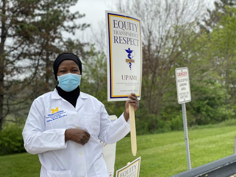 Simbiat Monsur, physician assistant at Michigan Medicine, holds a sign in support of colleagues negotiating a contract with the health system on May 4, 2021.