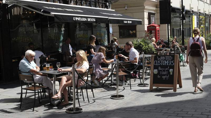 """FILE - In this Monday, Aug. 3, 2020 file photo, a sign outside a pub reads: """"Wanted Customers"""" in central London. The British economy recouped some further lost ground during July after a swath of coronavirus restrictions were lifted, official figures showed Friday Sept. 11, 2020. However, it still has to make up around half the output lost at the peak of the lockdown and now faces renewed risks related to Brexit. (AP Photo/Alastair Grant, file)"""