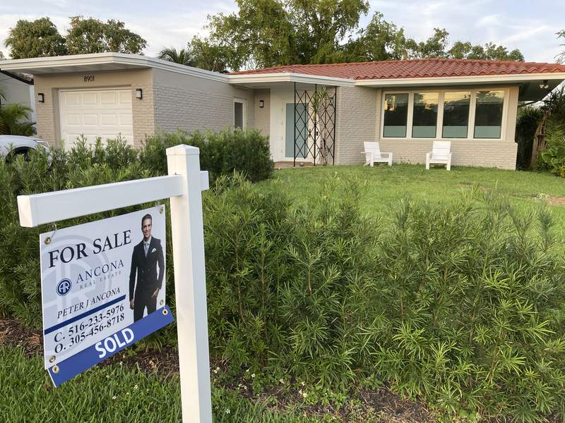 """A home with a """"Sold"""" sign is shown, Sunday, May 2, 2021, in Surfside, Fla.   Mortgage rates rose this week, pushing the benchmark 30-year home loan to the 3% mark for the first time since mid-April. Signs continued of the economys recovery from the pandemic recession and a burst of inflation rattled stock markets.   (AP Photo/Wilfredo Lee)"""