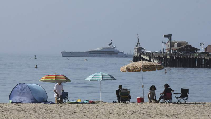 Early beachgoers secure spots on the shore at Santa Barbara, Calif., on Sunday, Aug. 16, 2020, as the superyacht Bravo Eugenia lies offshore. Californians packed beaches, lakes and recreation areas Sunday to seek relief from a record heat wave that strained the electricity grid and threatened to trigger a third round of rolling power outages. The heat wave brought triple-digit temperatures and raised wildfire danger and fears of coronavirus spread  a major concern in a state that has seen more than 621,000 confirmed cases. Public health officers urged people to follow mask and social distancing orders if they head outdoors. (AP Photo/John Antczak)
