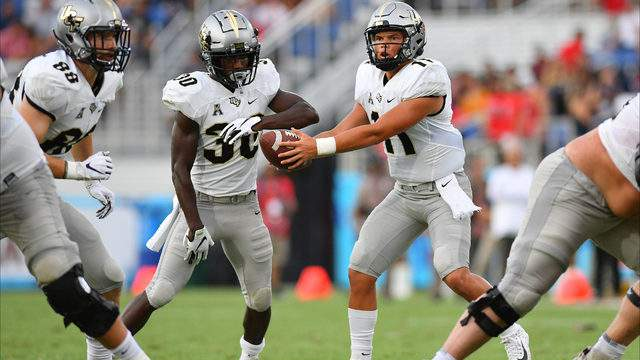 Dillon Gabriel #11 of the UCF Knights hands the ball off to Greg McCrae #30 the first half against the Florida Atlantic Owls at FAU Stadium on September 07, 2019 in Boca Raton, Florida. (Photo by Mark Brown/Getty Images)