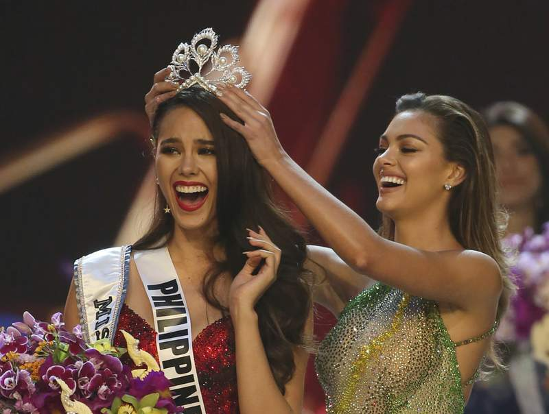 FILE - Catriona Gray of the Philippines, left, reacts as she is crowned the new Miss Universe 2018 by Miss Universe 2017 Demi-Leigh Nel-Peters during the final round of the 67th Miss Universe competition in Bangkok, Thailand, on Dec. 17, 2018. After a year and a half, the Miss Universe competition will return with a live telecast on May 16. The 69th Miss Universe will be crowned at the Seminole Hard Rock Hotel & Casino Hollywood. (AP Photo/Gemunu Amarasinghe, File)
