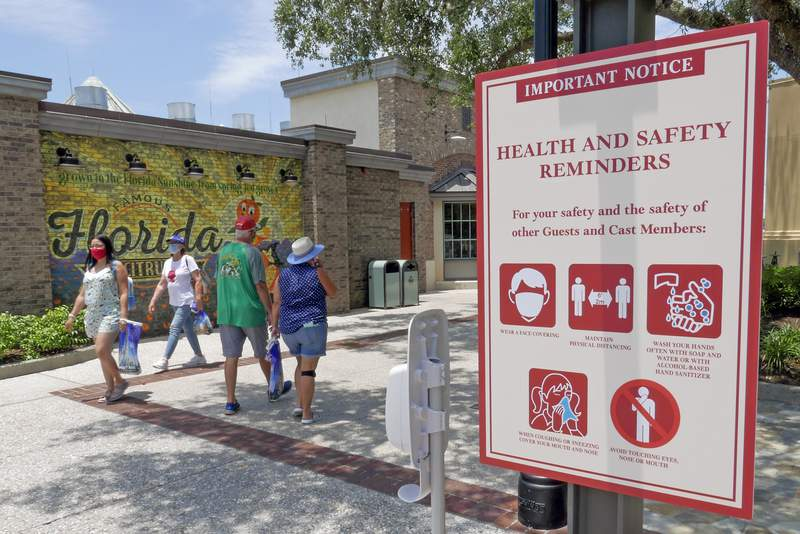Signs remind patrons to wear masks and other protocols because of the coronavirus pandemic as they stroll through the Disney Springs shopping, dining and entertainment complex Tuesday, June 16, 2020, in Lake Buena Vista, Fla. Walt Disney World Resort theme parks plan to reopen on July 11.(AP Photo/John Raoux)
