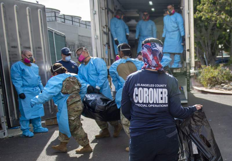 """This photo provided by the LA County Dept. of Medical Examiner-Coroner shows Elizabeth """"Liz"""" Napoles, right, works alongside with National Guardsmen who are helping to process the COVID-19 deaths to be placed into temporary storage at LA County Medical Examiner-Coroner Office on Tuesday, Jan. 12, 2020 in Los Angeles. More than 500 people are dying each day in California because of the coronavirus. The death toll has prompted state officials to send more refrigerated trailers to local governments to act as makeshift morgues. State officials said Friday they have helped distribute 98 refrigerated trailers to help county coroners store dead bodies. (LA County Dept. of Medical Examiner-Coroner via AP)"""