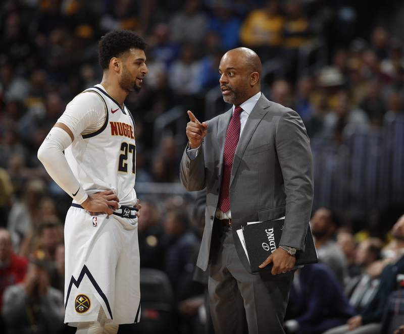 FILE - In this Sunday, March 1, 2020 file photo, Denver Nuggets guard Jamal Murray (27) confers with assistant coach Wes Unseld Jr. in the first half of an NBA basketball game. The Washington Wizards have named Wes Unseld Jr. as their next head coach. The Denver Nuggets associate coach is the son of Washington basketball legend Wes Unseld, whose number is retired and hangs in the rafters. Unseld Jr. replaces Scott Brooks who was fired after three playoff appearances in five seasons.(AP Photo/David Zalubowski, File)